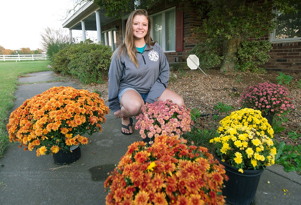 Seneca High School junior and budding entrepreneur Abby Meyer kneels near some of her mums waiting pick up at her Seneca home on Wednesday. Meyer grew about 400 plants this year and has sold most of her crop.<br /> Globe   Laurie Sisk