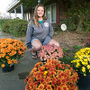 Seneca High School junior and budding entrepreneur Abby Meyer kneels near some of her mums waiting pick up at her Seneca home on Wednesday. Meyer grew about 400 plants this year and has sold most of her crop.<br /> Globe | Laurie Sisk