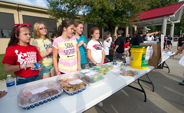 Baxter Springs Central Elementary sixth graders work a bake to sale to augment fundraising at their PTO's My School Color Run on Saturday at the school.<br /> Globe | Laurie Sisk