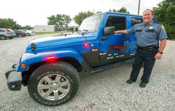 Ken Brodrick, Oklahoma D.A.R.E. coordinator, stands beside the Wyandotte Nation Police Department's D.A.R.E. Jeep last week at the department.<br /> Globe | Laurie Sisk