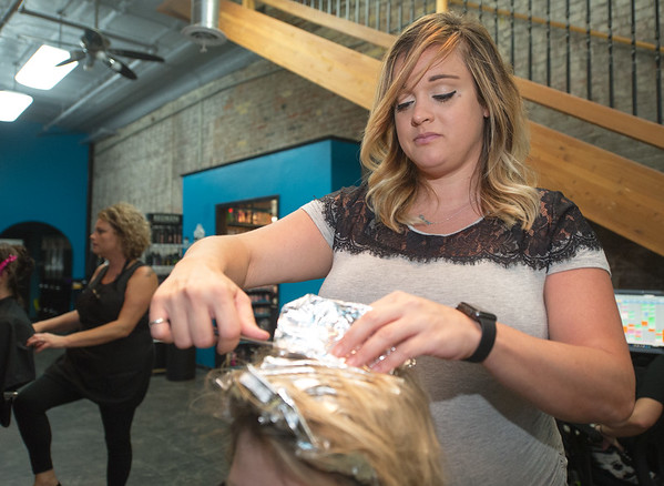 Salon 529 co-owner Heather Ward colors a clients hair in her shop at 529 S. Main St. on Wednesday. Ward is one of numerous business owners in downtown Joplin weighing in on proposed changes to downtown parking.<br /> Globe | Laurie Sisk