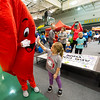 Five-year-old Ella Jo McDaniel, of Seneca, gets a heart-felt high five from a mascot on Saturday during The American Heart Association's Heart Walk at Leggett& Platt.<br /> Globe | Laurie Sisk