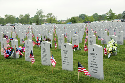 HALEE HEIRONIMUS / GAZETTE American flags, flowers and other memorial pieces were staked by gravestones of fallen military leaders at Ohio Western Reserve National Cemetery.