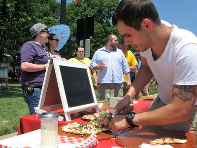 BOB SANDRICK / GAZETTE Bill Dalton, of Pizza 800 Degrees in Liverpool Township, slices pizza samples Saturday during Pizza Palooza on Public Square.