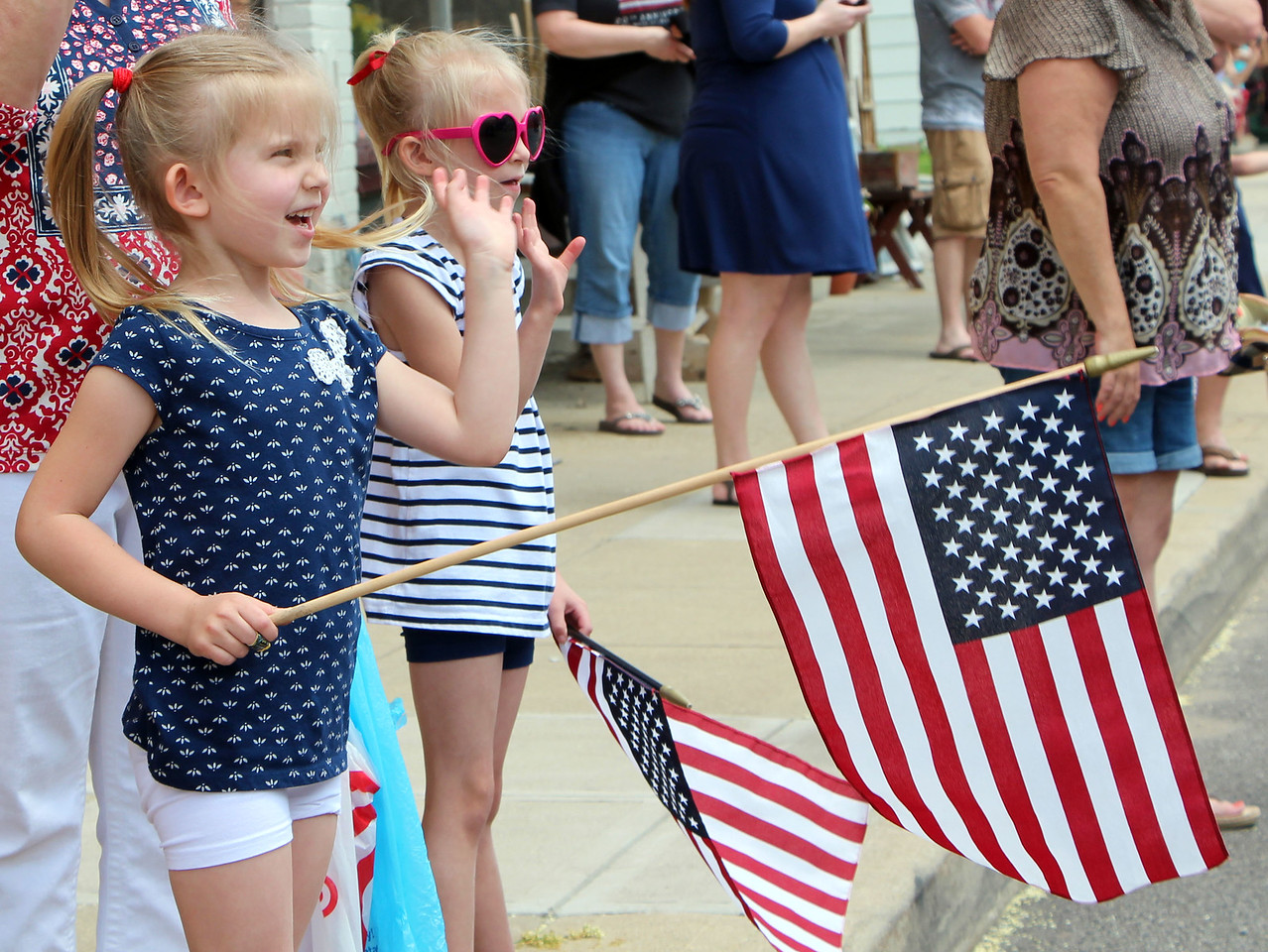 HALEE HEIRONIMUS / GAZETTE Sisters Harlow, 5, (front) and Finley Johnson, 7, (back) of Seville waved as the parade went down Main Street in Seville on Monday afternoon.