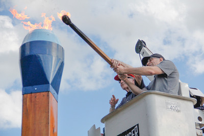 ALEC SMITH / GAZETTE Joe Gabrosek (left) and Gene Kovack light the Blue Tip torch Wednesday to signify the opening of the 2017 Blue Tip Festival in downtown Wadsworth.