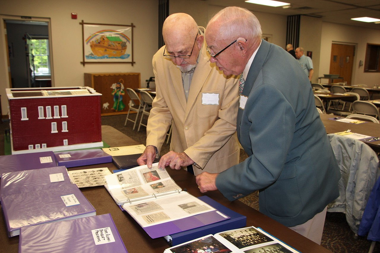 HALEE HEIRONIMUS / GAZETTE John Veres, left, and Bill Schultz, right, both from the class of 1950, look through an album of obituaries of previous classmates at York High School.