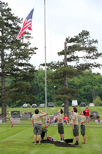 HALEE HEIRONIMUS / GAZETTE Boy Scout Troop 500 of York Township raises the flag in the York Township Cemetery on Norwalk Road Sunday afternoon as part of the Memorial Day ceremony.