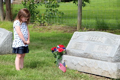 HALEE HEIRONIMUS / GAZETTE Charlie Bernard, 5, pays her respects to her great-grandfather, Kenneth Meeks, who was a World War II veteran, at the York Township Cemetery on Norwalk Road.
