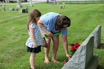 HALEE HEIRONIMUS / GAZETTE Dolly Bernard, Medina, and her granddaughter Charlie Bernard, 5, place flowers at the site of Dolly Bernard's father, Kenneth Meeks. Meeks was a World War II veteran.