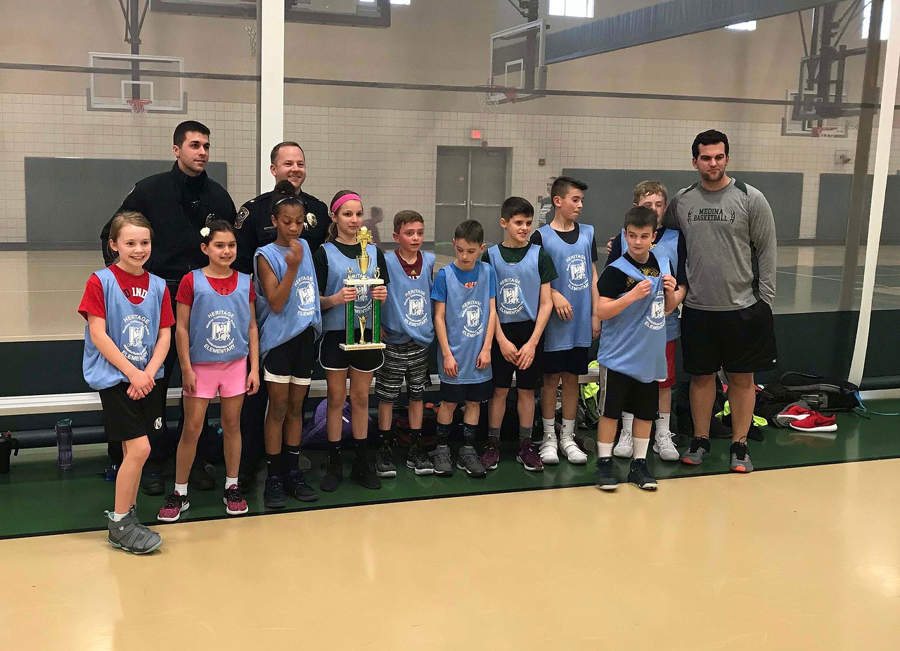 NATHAN HAVENNER / GAZETTE  Fifth-graders from Medina Schools' Heritage Elementary are the winners of the 2018 Medina County Police Activities League March Madness Basketball Tournament against the school district's Garfield Elementary on Thursday.