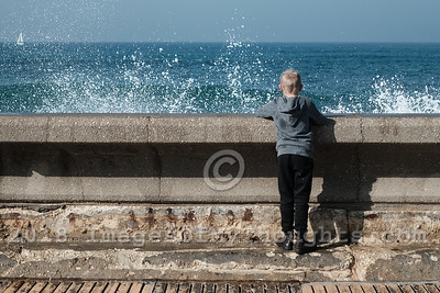 A young boy enjoys the spray of breaking waves at the Jaffa Port.