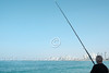A fisherman tries his luck at the Jaffa Port with the Tel Aviv skyline in the background.
