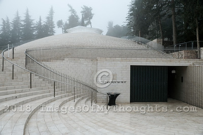"The National Memorial Hall For Israel's Fallen, within the Mount Herzl Military Cemetery in Jerusalem, opened to the public in October 2017, was erected to create an intimate space for a personal and collective experience of commemoration. Designers Kimmel Eshkolot Architects formed a 250 meter long continuous ""Wall of Names"" that wraps around the central sculptural brick structure and includes over 23,000 bricks engraved with the names of members of Israel's security services killed in the line of duty. Above the hall a funnel shaped formation of bricks opens to the sky, flooding the void with natural light."