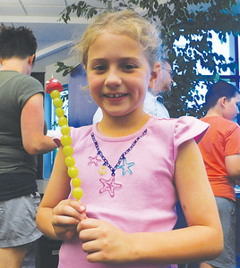 Seven-year-old Olivia Pedmo, of Litchfield Township, shows off her grape caterpillar Tuesday during Family Food Fest at Buckeye Library in York Township. JONATHAN DELOZIER / GAZETTE