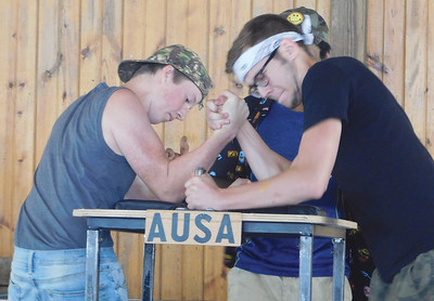 Clay Cooper III, of East Canton, right, earns a first round victory of Ethan Zietlow of Wellington at Arm Wrestling USA's Ohio State Championship at the Medina County Fair. JONATHAN DELOZIER / GAZETTE