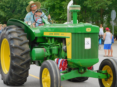 BOB FINNAN / GAZETTE This man, with his son on his lap, is driving his John Deere tractor in the Valley City Fourth of July parade Thursday on state Route 303.