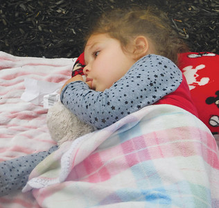 JONATHAN DELOZIER / GAZETTE Four-year-old Camryn Taylor of Smithville takes a nap amid the ongoing parade. A two-mile parade with more than 100 entries officially began Wadsworth's 46th annual Blue Tip Festival on Tuesday.