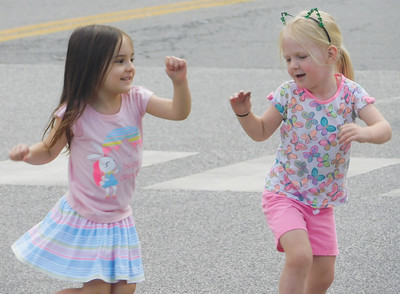 JONATHAN DELOZIER / GAZETTE Macie Delnoce and Kate Lally of Wadsworth dance as they wait for the parade to begin. A two-mile parade with more than 100 entries officially began Wadsworth's 46th annual Blue Tip Festival on Tuesday.