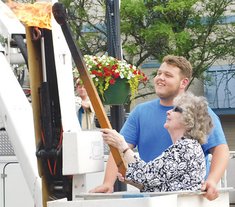 JONATHAN DELOZIER / GAZETTE Parade grand marshal Marian Mochel is lifted up to light the ceremonial match. A two-mile parade with more than 100 entries officially began Wadsworth's 46th annual Blue Tip Festival on Tuesday.
