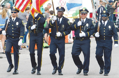 JONATHAN DELOZIER / GAZETTE Wadsworth police officers wave hello to a packed downtown. A two-mile parade with more than 100 entries officially began Wadsworth's 46th annual Blue Tip Festival on Tuesday.