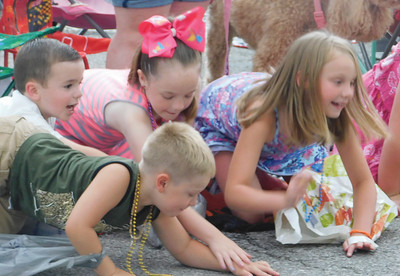 JONATHAN DELOZIER / GAZETTE Holden Porter of Jeromesville, Cayden Brown of Wadsworth, Taylor Brown of Wadsworth, and Gracelynn Owensby of Wadsworth scramble to gather candy. A two-mile parade with more than 100 entries officially began Wadsworth's 46th annual Blue Tip Festival on Tuesday.