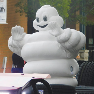 JONATHAN DELOZIER / GAZETTE Van's Auto Service and the Michelin Man wave to onlookers. A two-mile parade with more than 100 entries officially began Wadsworth's 46th annual Blue Tip Festival on Tuesday.