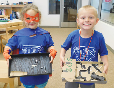 JONATHAN DELOZIER / GAZETTE Kaci Nolin, 6, and Colin Tomsho, 7, both of Wadsworth, finish their marble mazes at Wadsworth High School during STEM Summer Camp