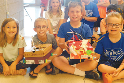 JONATHAN DELOZIER / GAZETTE Ella Hamm, 9; Chase Ulis, 7; Evan Johnston, 10; and Hampton Davis, 8, show off their newly created rover vehicles at Wadsworth High School during STEM Summer Camp.