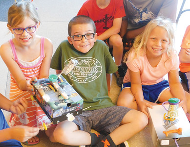 JONATHAN DELOZIER / GAZETTE Leila Hughes, 8; Gavin Archinal, 8; and Anna Serra, 9, point out simple machines they worked into their projects at Wadsworth High School during STEM Summer Camp.
