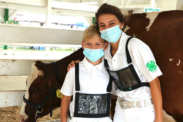 Owen and Lydia Nisen, Goshen, pose for a photo before showing their heifers at the Elkhart County 4-H Fairgrounds Friday.