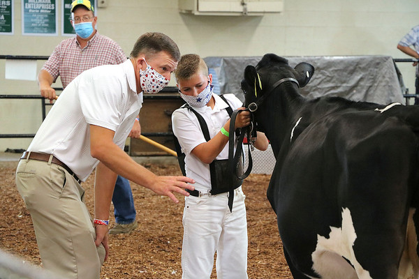 Judge Jeff Price talks with exhibitor Ethan Miller during the showmanship competition Friday at the Elkhart County 4-H Fairgrounds.