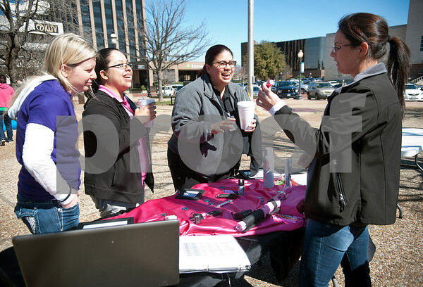 """photo by Sarah A. Miller/Tyler Morning Telegraph  Amber Leach of Damsel in Defense, shows off her company's products such as a stun gun disguised as a cell phone during One Billion Rising, a national fun protest against women's violence that was held on the square in downtown Tyler Thursday afternoon. The name One Billion Rising comes from the statistic from the 2003 UNIFEM report entitled """"Not A Minute More: Ending Violence Against Women"""" that one in three women on the planet will be raped or beaten in her lifetime. The movement aims to quell the acceptance against rape and violence to women globally. Pictured left to right are Annie Moch, Veronica Anguirano and Melissa Torres."""