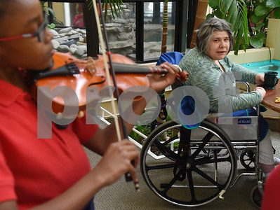 Resident Cheryl Fisher listens as violin students from St. Gregory Cathedral School play music during lunch at Park Place Nursing & Rehabilitation Center Tuesday Feb. 14, 2017.  (Sarah A. Miller/Tyler Morning Telegraph)