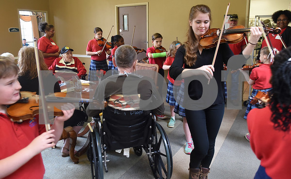 St. Gregory Cathedral School violin students under the direction of teacher Abby Jorden, center, play music during lunch at Park Place Nursing & Rehabilitation Center Tuesday Feb. 14, 2017.  (Sarah A. Miller/Tyler Morning Telegraph)