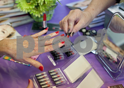 photo by Sarah A. Miller/Tyler Morning Telegraph  Avon representative Susie Ripkowski, owner of Love's Nest in Jacksonville, matches a lipstick to Gallatin resident Kaye Bostock's freshly painted fingernails at Cherokee County Relay For Life's annual spa day at the Rusk Civic Center Tuesday. Bostock and other cancer survivors as well as caregivers to people with cancer were invited to attend the pampering event.