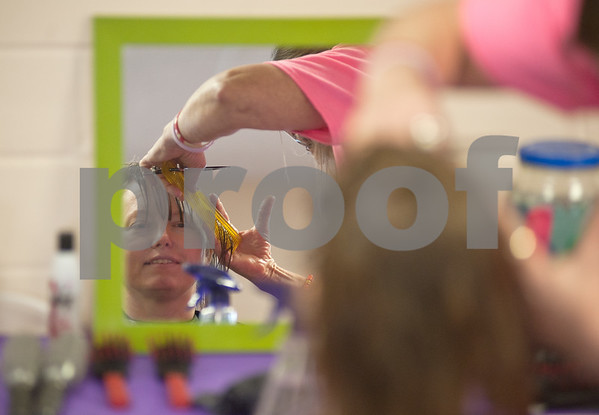 photo by Sarah A. Miller/Tyler Morning Telegraph  Amy McCalister of Rusk has her hair cut by Cheryl Reynolds of Ironton at Cherokee County Relay For Life's annual spa day at the Rusk Civic Center Tuesday. McCalister was diagnosed with cancer in 2001 and Reynolds is a 25 year cancer survivor and the owner of Cheryl's Retro Hair Salon.