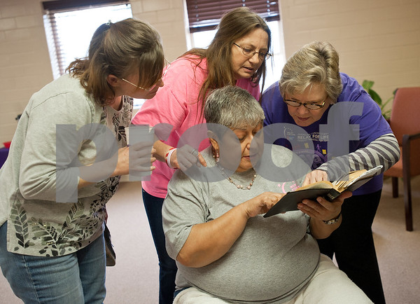 "photo by Sarah A. Miller/Tyler Morning Telegraph  Diana Vega of Jacksonville holds a Bible as she takes a break from washing feet to look up Romans 10:15, ""How beautiful are the feet of those who preach the gospel of peace"" with help from Amy McCalister of Rusk, left, Cheryl Reynolds of Ironton, center, and Brenda Hendrickson of Ponta, right during the Cherokee County Relay For Life's annual spa day at the Rusk Civic Center Tuesday. Volunteers at the event washed feet, gave facials, did nails, makeup and gave massages to cancer survivors and caner caregivers."