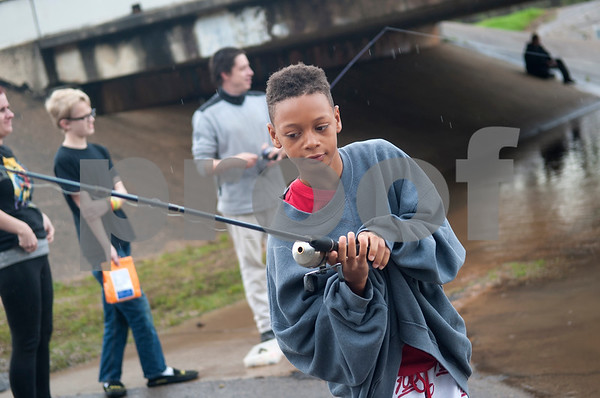 Isaiah Moore, 10, of Longviewm gets ready to cast his fishing line at River Park in Chandler, Texas Saturday March 12, 2016. Rainy conditions did not stop several dozen fishers from coming to the park, situated along the Niches River, to catch sand bass and catfish.  (Sarah A. Miller/Tyler Morning Telegraph)