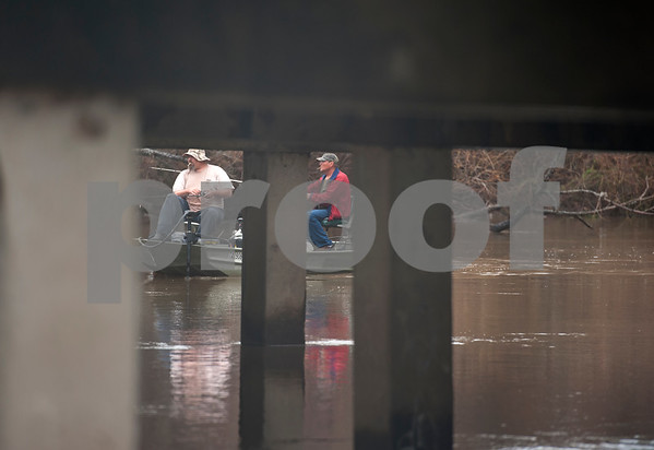Two men use a boat to fish at River Park in Chandler, Texas Saturday March 12, 2016. Rainy conditions did not stop several dozen fishers from coming to the park, situated along the Niches River, to catch sand bass and catfish.  (Sarah A. Miller/Tyler Morning Telegraph)