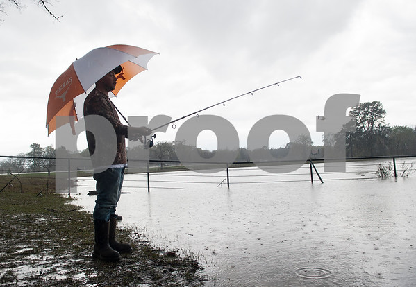 """Romeo Peña of Tyler fishes over the flooded nature trail area at River Park in Chandler, Texas Saturday March 12, 2016. Rainy conditions did not stop several dozen fishers from coming to the park, situated along the Niches River, to catch sand bass and catfish. """"Sometimes the water floods all the way to the parking lot,"""" Peña said.  (Sarah A. Miller/Tyler Morning Telegraph)"""