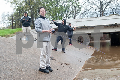 Jon Vandagriff of Palestine, center, fishes at River Park in Chandler, Texas Saturday March 12, 2016. Rainy conditions did not stop several dozen fishers from coming to the park, situated along the Niches River, to catch sand bass and catfish.  (Sarah A. Miller/Tyler Morning Telegraph)