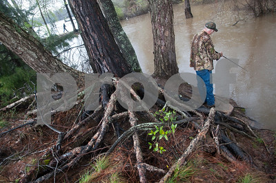 """James Johnson of Athens fishes at River Park in Chandler, Texas Saturday March 12, 2016. Rainy conditions did not stop several dozen fishers from coming to the park, situated along the Niches River, to catch sand bass and catfish. """"I haven't fished in a long time because I work so much. My dad used to take me fishing, and it didn't matter what the weather was,"""" Johnson said.  (Sarah A. Miller/Tyler Morning Telegraph)"""