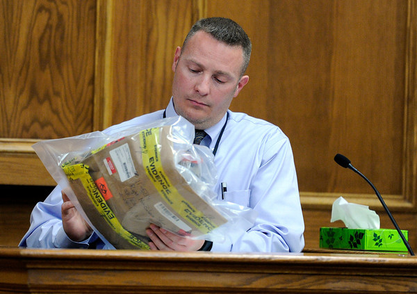 """Raszynski Trial014.JPG Lafayette police detective Scott Robinson looks at a shoe that was submitted as evidence during the Adam Raszynski trial on Wednesday, March 14, at the Boulder County Justice Center in Boulder. Rasynski is accused of stomping his mother, Rita Redford, to death after she shot him five times. For more photos of the trial go to  <a href=""""http://www.dailycamera.com"""">http://www.dailycamera.com</a><br /> Jeremy Papasso/ Camera"""