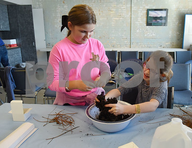 Tilly McFarlin, 9, of Bullard, and Mia Saxon, 9, of Tyler, mix soil to create bricks during spring break camp at Discovery Science Place Tuesday March 14, 2017.  (Sarah A. Miller/Tyler Morning Telegraph)