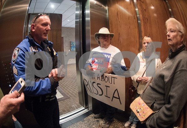 Tyler Police speak with demonstrators in the elevator as they leave U.S. Sen. John Cornyn's office in Tyler Wednesday March 15, 2017. The demonstration was organized by Indivisible of Smith County, a group which is asking senators to vote against the Republican plan to replace the Patient Protection and Affordable Care Act, also known as Obamacare.  (Sarah A. Miller/Tyler Morning Telegraph)