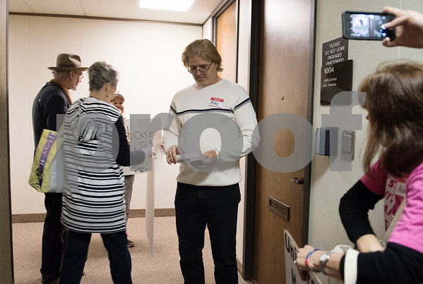 Mike Nichols hands out cards for demonstrators to leave notes on the door to U.S. Sen. John Cornyn's office in Tyler Wednesday March 15, 2017 after their attempts to ring the doorbell were unanswered. The demonstration was organized by Indivisible of Smith County, a group which is asking senators to vote against the Republican plan to replace the Patient Protection and Affordable Care Act, also known as Obamacare.  (Sarah A. Miller/Tyler Morning Telegraph)