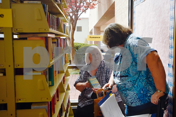 Linda Taylor shows her sister Vera Forrester a book during a spring book sale at the Tyler Public Library in Tyler, Texas, on Wednesday, March 15, 2017. The bi-annual sale, which runs through Sunday, includes thousands of adult and children's fiction and non-fiction books, as well as audio books, music cassettes and videotapes, most of which is priced at one dollar or less. (Chelsea Purgahn/Tyler Morning Telegraph)