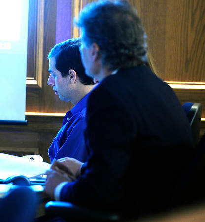 Adam Raszynski looks over paperwork in a darkened courtroom during his trial on Friday March 16, 2012 at the Boulder County Justice Center. Raszynski, is charged with murdering his mother in Lafayette after being shot by her just over a year ago.<br /> Photo by Paul Aiken / The Boulder Camera