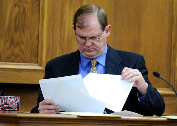 Boulder and Adams County Forensic Pathologist Michael Arnall looks through a series of pictures used as evidence on Friday, March 16, during the third day of the Adam Raszynski murder trial at the Boulder County Justice Center in Boulder. Raszynski is on trial for the murder of his mother Rita Redford.<br /> Jeremy Papasso/ Camera